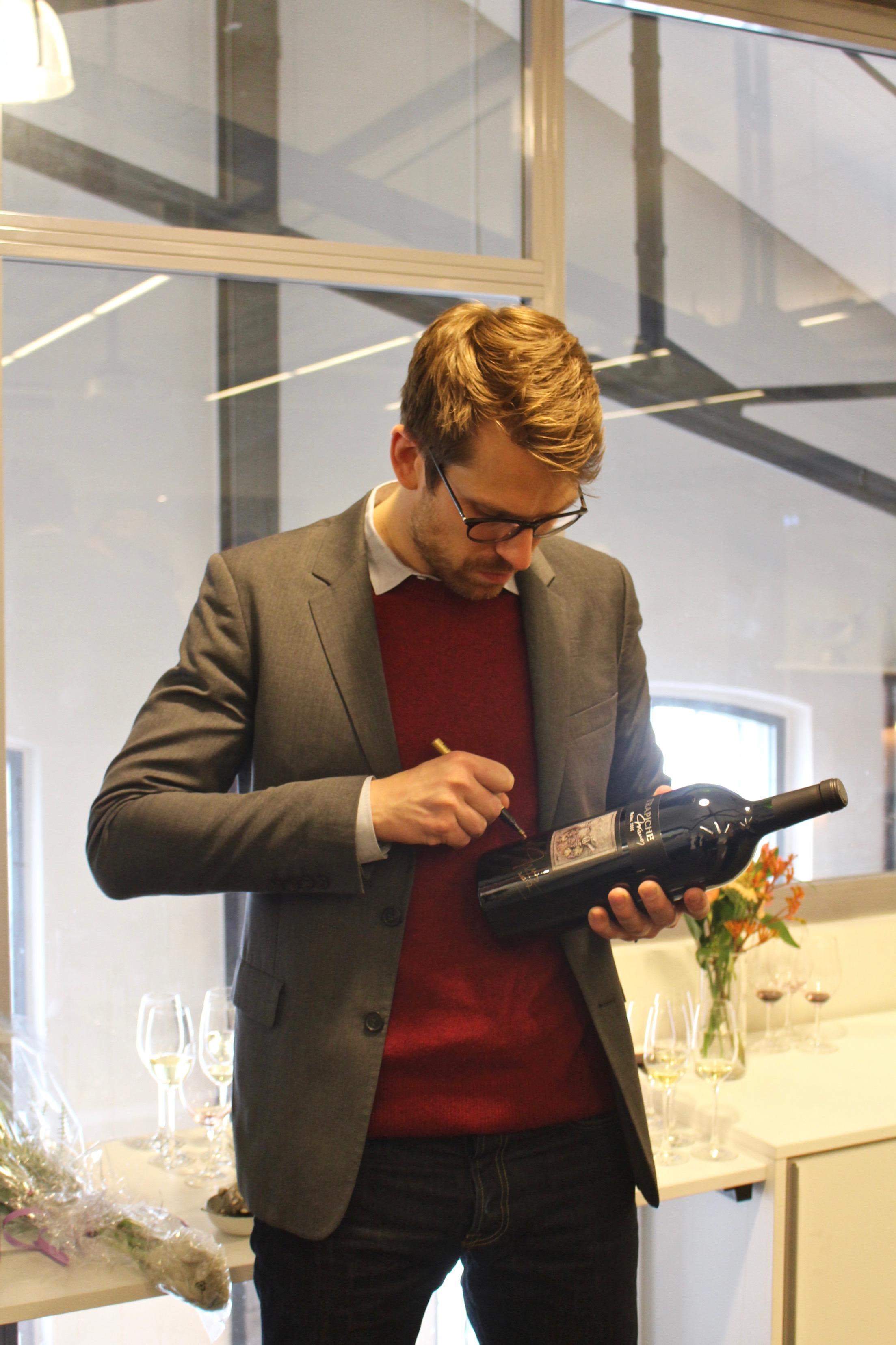 Arvid Rosengren signerar vinflaskor till en välgörenhetsauktion.
